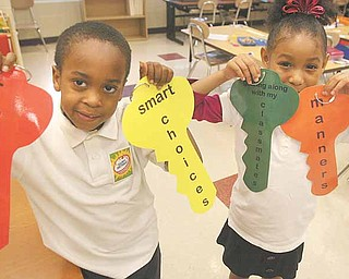 Taft Elementary School kindergartners, from left, Brea'on Slocum and Reagan Nevels hold keys designating characteristics they've learned about in Project KIND. The program by Community Solutions Association on Thursday presented the last of 12 weekly sessions.