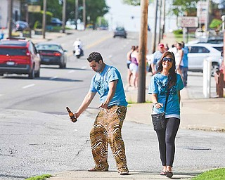 Jonathan Kanos of Poland and Kelly Johnson of Girard enjoy the sun and high temperatures that prevailed for the shuffle as they walk from one bar to the next. More than 400 people took part in the event.
