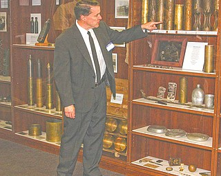 Joel Parkinson, curator of the World War History museum in Alliance,  points out exhibits of war relics at the museum. A tour for officials and the press took place there Saturday.