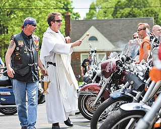 The Rev. Gregory Maturi blesses and sprinkles holy water on motorcycles with the help of his altar assistant, Randy Blakeman of Austintown, on Saturday afternoon at St. Dominic Church.