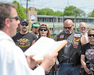 The Rev. Gregory Maturi offers a prayer to more than 70 motorcyclists who attended a motorcycle blessing Saturday at St. Dominic Church on the city's South Side.