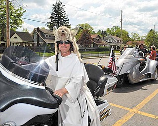 Father Maturi strikes a pose on a motorcycle and dons a helmet brought by a cyclist who attended Saturday's blessing.
