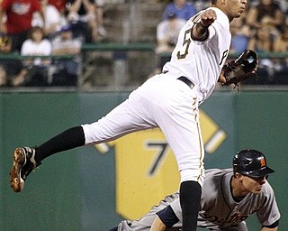 Pittsburgh Pirates shortstop Ronny Cedeno (5) hops to avoid Detroit Tigers' Brandon Inge while completing a double play on Tigers' Austin Jackson in the ninth inning to end an interleague baseball game on Saturday, May 21, 2011, in Pittsburgh. The Pirates won 6-2.