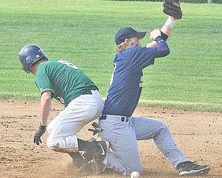 Ursuline's Anthony Rohan slides safely into the bag as Brookfield's Cameron Derr bobbles the ball during their Division III district semifinal baseball game Monday at Cene Park in Struthers. The Irish dominated the Warriors 18-1 to advance the district final against Champion today at Cene Park.