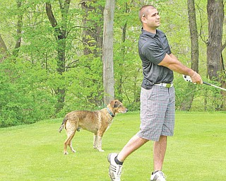 Chris LaCivita takes a shot at Hole 12 at Deer Creek. The family dog joined him on the course.
