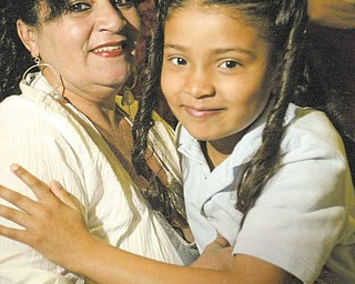 Ashley Cruz, a second grader at Williamson Elementary School, hugs her mom, Elizabeth Cruz, during a program celebrating mothers at the school on Monday.