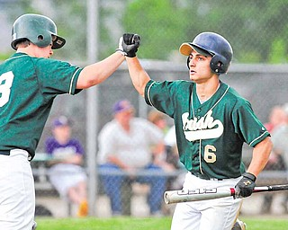 Ursuline's Anthony Rohan (6) is congradulated by teammate Sam Donko after scoring the first run of the game on Tuesday. The Irish defeated Champion 14-1 in the Division III district championship game at Cene Park.