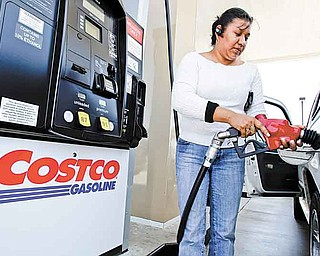 A customer pumps gas at a Costco station in Redwood City, Calif., Tuesday, May 24, 2011. Costco's net income rose 6 percent in its fiscal third quarter, with growing membership numbers pushing sales both at home and abroad. (AP Photo/Paul Sakuma)