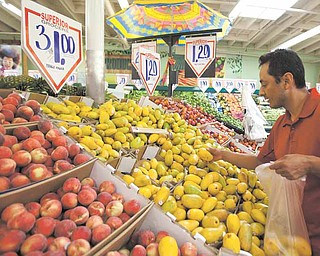 In this May 23, 2011 photo, customer Gabriel Sanchez shops for fresh fruit at a Superior Grocers store in Los Angeles. Consumer spending rises but much of gain goes to pay for higher food and energy Friday, May 27, 2011.(AP Photo/Damian Dovarganes)