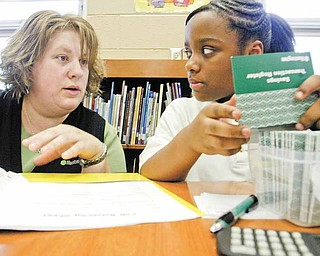 Cierra Dandridge, a fifth-grader at Taft Elementary School, and Kandie Kline, a Huntington Bank area operations specialist, prepare for the school's twice-monthly Kids Club program. The Huntington Bank program teaches children skills in financial literacy.