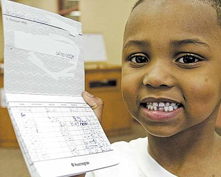 At right, Taft Elementary School kindergartner Michael Logan shows the bank book he's been using to keep track of deposits to his savings account. The Kids Club, a banking program from Huntington Bank, allows children to learn about saving money and the operations of a bank.