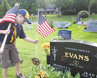Jack Brant, 8, of Poland honors World War II veteran Sennett C. Evans by placing a flag at his gravesite in Poland Riverside Cemetery on Saturday afternoon in anticipation of Monday's Memorial Day holiday.