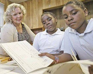 William D Lewis The Vindicator Tutor Helen Italiano works with sisters  and Naferteria, left, and Treasure Green during a tutoring session at the Rescue Mission where they live.