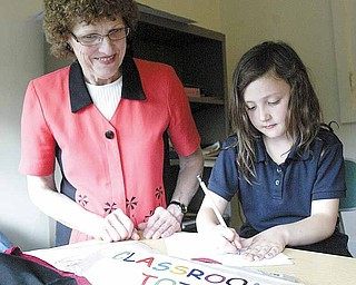 Jean White works with Corra Koellner, 7, during a tutoring session at Beatitude House.