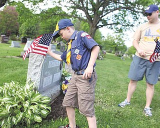 Jack Brant, 8, and his father, Chad Brant, both of Poland, place flags at the graves of veterans Saturday at Poland Riverside Cemetery. Jack is a member of Cub Scout Pack 44,  one of several groups performing the annual pre-Memorial Day task at the cemetery.