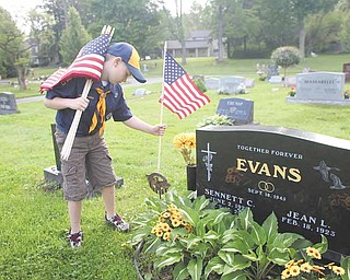 Leslie Cusano | The Vindicator.Jack Brant, 8 of Poland places a flag at the grave of a World War II veteran at Poland Riverside Cemetary Saturday. Jack is in Cub Scout Troop 44, one of the groups who attended the event.