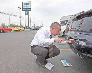 Dustin Hager moves license plates from one car to a new Chevy he sold at Hank Graff Chevrolet in Davison, Michigan, on May 13, 2011. (Eric Seals/Detroit Free Press/MCT)
