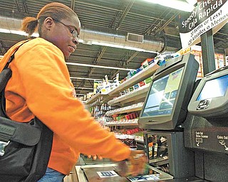 Tifany Greendge uses a self-serve checkout counter at a Wal-Mart Neighborhood grocery store in Orlando, Florida, in 2006. Wal-Mart  is taking the neighborhood grocery store concept, now called Wal-Mart Market, around the country. (Dennis Wall/Orlando Sentinel/MCT)