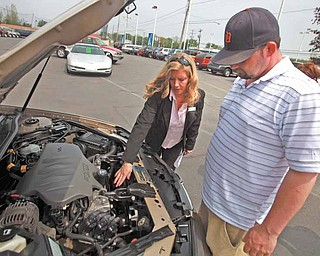 After the test drive Craig Kehoe, right, and sales person Debbie Schlegelmilch go over some details of the used car at Hank Graff Chevrolet in Davison, Michigan, on May 13, 2011. (Eric Seals/Detroit Free Press/MCT)..