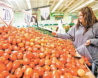 In this May 23, 2011 photo, consumer Sonia Romero shops for tomatoes at a Superior Grocers store in Los Angeles. A monthly survey shows consumers are losing faith that the economy will keep improving. (AP Photo/Damian Dovarganes)
