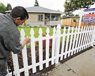 A man cleans a fence at a house for sale in East Palo Alto, Calif., Monday, May 31, 2011. Home prices fell nationwide for the eighth straight month, according to the Standard & Poor's/Case-Shiller 20-city index released Tuesday. Home prices in major areas have reached their lowest level since the U.S. housing bubble burst in 2006, stymied by foreclosures, a surplus of unsold homes and continued reluctance of Americans to buy homes. (AP Photo/Paul Sakuma)