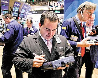Louis Silk, center, and other traders work on the floor of the New York Stock Exchange, Tuesday, May 31, 2011. (AP Photo/Richard Drew)