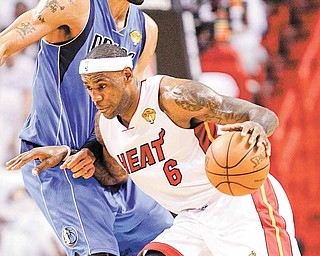 Miami Heat's LeBron James (6) dribbles pass Dallas Mavericks Tyson Chandler, during the first half of Game 1 of the NBA Finals basketball game Tuesday, May 31, 2011, in Miami. (AP Photo/David J. Phillip)