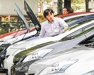"""FILE - In this May 13, 2011 file photo, an employee of Toyota Motor Corp. cleans the """"Prius a,"""" or """"Prius alpha,"""" a revamp of its popular gas-electric hybrid, during its launch in Tokyo. Toyota Motor Corp. said Wednesday, June 1, 2011, May U.S. car and truck sales fell 33 percent over the same month last year as the automaker was hit by earthquake-related shortages. (AP Photo/Koji Sasahara, file)"""