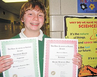 """Science comes naturally to him: Brennan Bizon holds two certificates he received from The Ohio Academy of Science for Superior ratings he earned for his science project, """"Which Ball Bounces Higher?"""" Brennan, a seventh-grader at Holy Family School in Poland, earned a Superior rating at the school's science fair before going on to win the academy awards at the Lake-to-River District Science Day at Youngstown State University and the State Science Day at Ohio State University in Columbus. He said he was inspired by basketball to find out whether a larger or a smaller ball bounces higher."""
