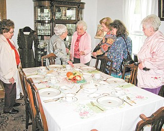 Pattern with a purpose: Cecilia Cooper, center, explains the history of the British Ironstone tea-leaf pattern dinnerware on display at the Hubbard Historical Society's McBride House, at 27 Hager St., to members of the Coitsville-Campbell Homemakers. The group toured the house recently. There is no open house scheduled at McBride for the month of June. Arrangements to tour the house can be made by phoning Cooper at 330-534-4247.