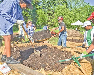 Elisabeth Stocking of St. Louis and Maurice Small of Cleveland dump a load of leaf compost into a raised garden plot for a new community garden on the East Side of Youngstown.