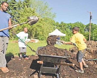 Johnny Eiland, left, Keith Foster, 10, and Samuel Rivera, 9, of Youngstown shovel soil into a wheelbarrow to use for a raised-bed garden plot.