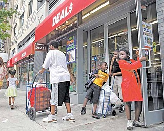 In this photo taken May 29, 2011, Teyonce Armstrong, right, 7, and her brothers Keith, 6, and Markquis, 11, play by the door of a Harlem Deal$ store in New York while waiting for their grandmother, who was shopping inside, to exit.  Deal$ stores are owned by Dollar Tree, which sells a variety of items for $1. The company said at the end of May it continues to see more customers who are spending more per visit.  Dollar stores pose the biggest threat Wal-Mart, the nation's biggest retailer. (AP Photo/Kathy Willens)