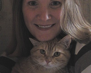 """Carole Sharp of Austintown says: """"After volunteering for Angels for Animals, a 5-year-old orange tabby chose me this February. His name is Romeo, and he came into our home with two boys, a dog from the pound, a rescued retriever and another cat, also from the shelter, to play with. I thought he chose me, but when I brought him home, he chose my husband instead. I've heard you don't choose the cat. The cat chooses you. I believe it now. The one who chooses you is the one who really wants to stay by your side. Rescued cats seem to be more affectionate and really crave attention that warms your heart. Our other cat is his best friend, and they play together all the time. Seeing what I see now, I'll never have just one. I never realized how lonely our cat was until we brought Romeo home. They really need companions, just like us."""""""