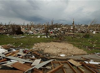 Andrea Schemet pauses while salvaging items from a destroyed home belonging to a friend's mother-in-law in Joplin, Mo. Friday, May 27, 2011. An EF-5 tornado tore through much of the city Sunday, damaging a hospital and hundreds of homes and businesses and killing at least 126 people. (AP Photo/Charlie Riedel)
