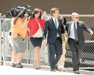 John Edwards, center, enters the Federal Building in downtown Winston-Salem, N.C. on Friday, June 3, 2011. A grand jury indicted the two-time presidential candidate on Friday, accusing him of trying to protect his political ambitions by soliciting and secretly spending more than $925,000 to hide his mistress and their baby from the public. (AP Photo/Winston-Salem Journal, Jennifer Rotenizer)