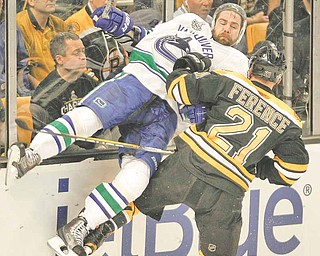 Boston Bruins defenseman Andrew Ference (21) checks Vancouver Canucks left wing Christopher Higgins (20) in the first period during Game 3 of the NHL hockey Stanley Cup Finals on Monday, June 6, 2011, in Boston.  (AP Photo/Winslow Townson)