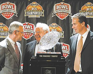 Ohio State head coach Jim Tressel, left, and Florida head coach Urban Meyer, right, are joined by former Ohio State coach Earle Bruce, center, as they stand with the BCS college football championship trophy Sunday, Jan. 7, 2007, in Scottsdale, Ariz. Florida will face Ohio State Monday in the BCS college football championship game. (AP Photo/Ted S. Warren)