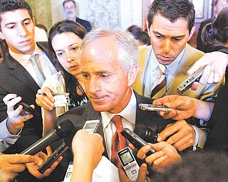 Sen. Bob Corker, R-Tenn., center, talks to the reporters on Capitol Hill in Washington, Wednesday, June 8, 2011, after the Senate voted  to let the Federal Reserve slice the fees that stores must pay banks each time a customer swipes a debit card, handing merchants a victory over banks in a lobbying battle over billions in revenue. (AP Photo/Jacquelyn Martin)