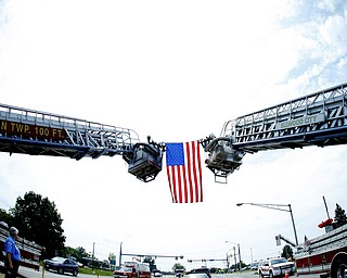 NEW CASTLE, PA - JUNE 11:  Lawrence County Fire Departments drape a flag between two ladder trucks as the funeral precession of Staff Sgt. Edward Mills Jr. passed under in Shenango Township on June 11, 2011 in New Castle, PA.  (photo by:  Justin K. Aller)