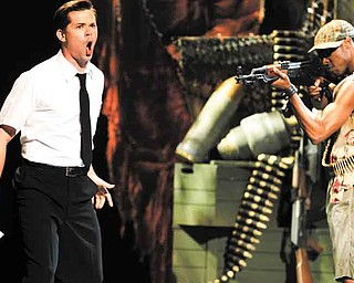 """Andrew Rannells, left, and the cast of """"The Book of Mormon"""" perform during the 65th annual Tony Awards, Sunday, June 12, 2011 in New York. (AP Photo/Jeff Christensen)"""