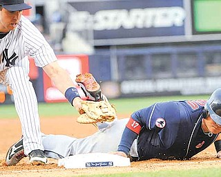 Cleveland Indians' Shin-Soo Choo, right, is safe at first on a pickoff attempt as he gets back to the bag before the tag by New York Yankees first baseman Mark Teixeira during the second inning of a baseball game Monday, June 13, 2011, at Yankee Stadium in New York. (AP Photo/Bill Kostroun)