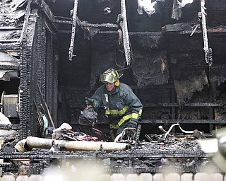 A firefighter looks for clues after a fire that killed four children and two adults in Warren. The fire at 911 Landsdowne Ave. NW was reported at 4:43 a.m. Thursday..