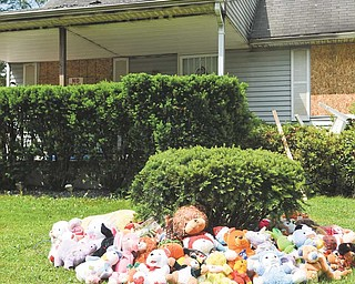 Teddy bears and other mementos are placed in memoriam around a shrub at 911 Landsdowne Ave. NW, Warren, where six people — two adults and four children — were killed in a Thursday morning house fire.