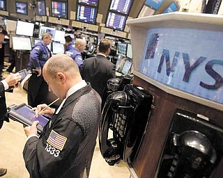 In this June 16, 2011 photo, traders work on the floor of the New York Stock Exchange. World markets fell Friday, June 17, despite positive economic data out of the U.S., as a political shake-up in Greece added to worries that the country might be forced to default on its debt. (AP Photo/Richard Drew)