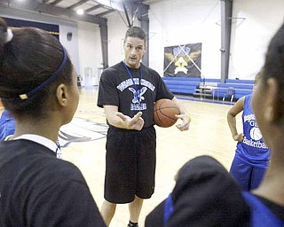 Bill Hoelzel, girls basketball coach at Youngstown Christian School, talks with his players