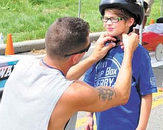 Jeff Johnson helps Victoria Romeo starp up her helmet before her race Saturday morning.