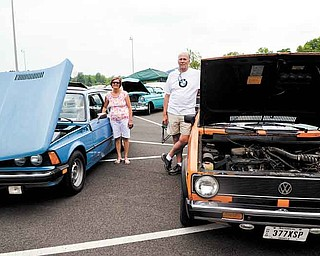 """Cindy Reynolds stands beside her 1978 BMW 320 and her husband, Rob, shows off his 1981 Volkswagen Rabbit convertible Sunday at the seventh annual Beaver Township Ruritan Father's Day car show. The couple says they are """"nuts"""" about cars."""