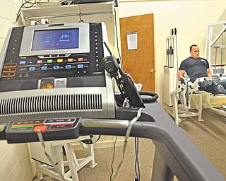 Hubbard Township Police Officer Greg Tarr works out on a leg machine in the new exercise room at Hubbard Township Police Department. The department received some donated equipment, and Fraternal Order of Police Lodge 85 bought other pieces including a treadmill, in foreground. Tarr said the exercise equipment will help increase officers' fitness.