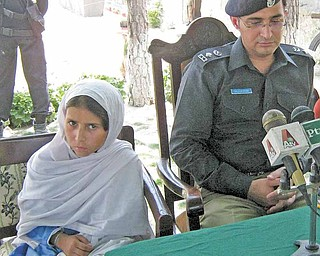 Sohana Jawed, left, a nine year old Pakistani girl sits with police chief Salim Marwat during a news conference in Lower Dir in Timergarah, Pakistan on Monday, June 20, 2011. A 9-year-old girl who was kidnapped on her way to school and forced to wear a suicide vest managed to escape her captors Monday as they directed her to attack a paramilitary checkpoint in northwest Pakistan. (AP Photo/M. A. Khan)